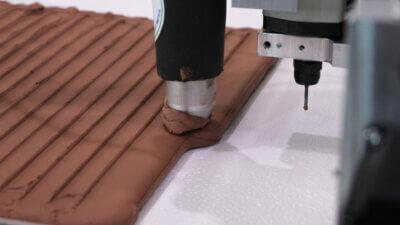 Clay wird automatisiert in gleichmäßigen Bahnen ohne Handarbeit aufgetragen